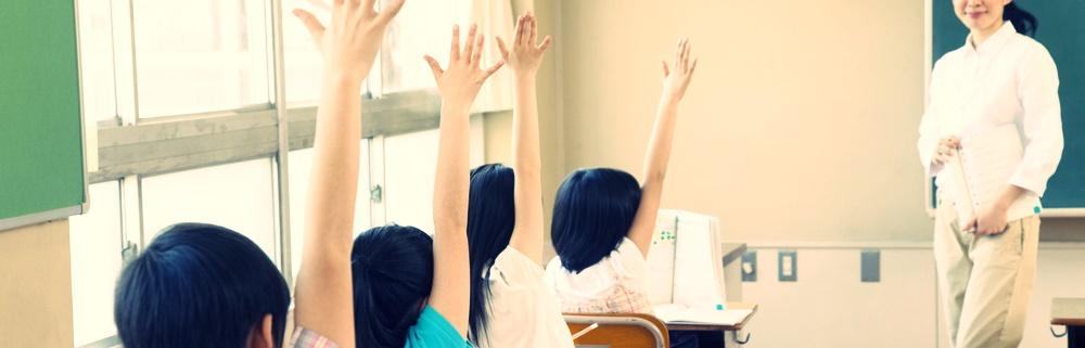 教室で手を挙げる子どもたち